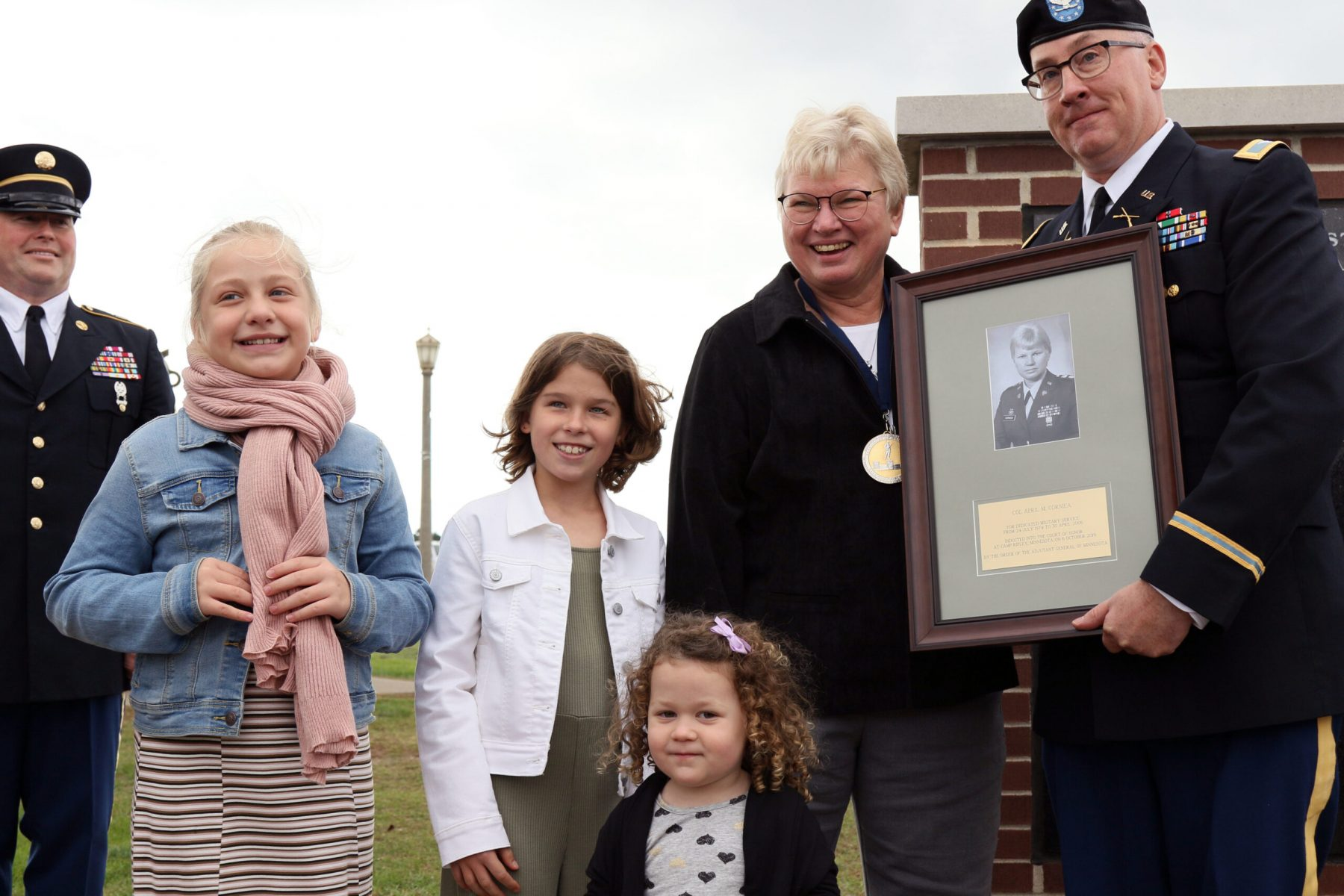 Colonel (Ret.) April M. Corniea poses with her family and plaque during the unveiling after the Court Of Honor Induction Ceremony on Camp Ripley on October 6th 2019.