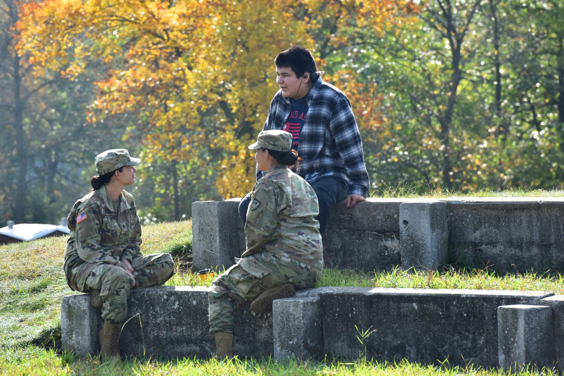 Minnesota National Guard Sgt. First Class Jessica Stiffarm (left) and Staff Sgt. Jennifer Stiffarm (right) share stories with a Mille Lacs Band of Ojibwe student from Onamia High School Sept. 20, 2019 during a 'Planting for the Future' cultural and informational exchange event on Camp Ripley.