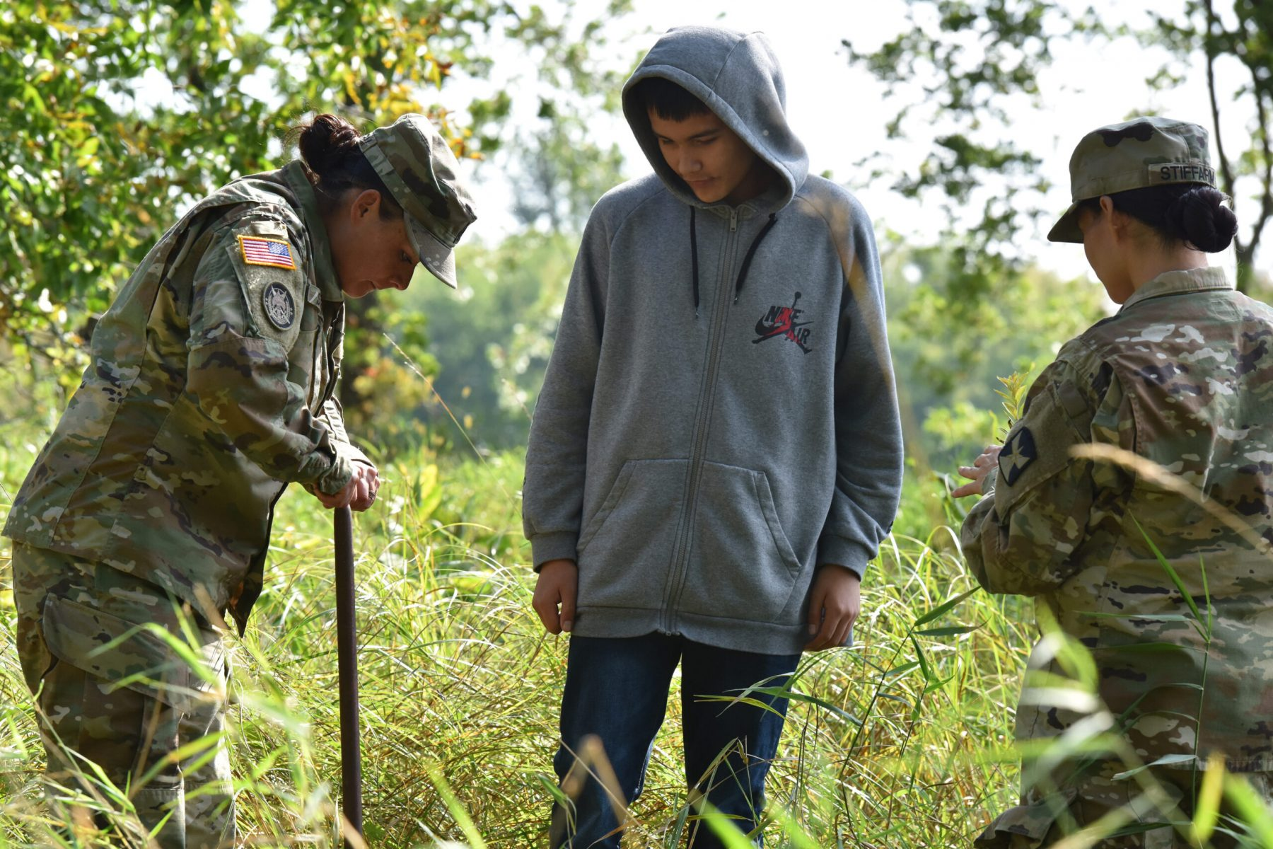 Minnesota National Guard Sgt. First Class Jessica Stiffarm (left) and Staff Sgt. Jennifer Stiffarm (right) work with a Mille Lacs Band of Ojibwe student from Onamia High School Sept. 20, 2019 to plant native plants on Camp Ripley during a 'Planting for the Future' cultural exchange event.